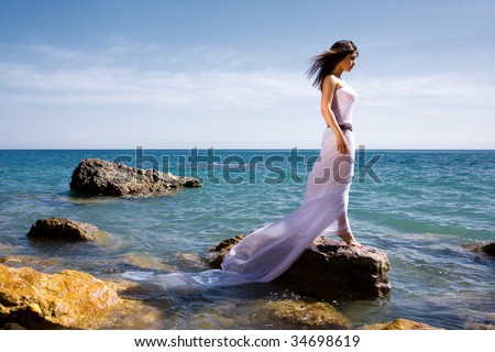 Beautiful woman in white dress at the sea beach
