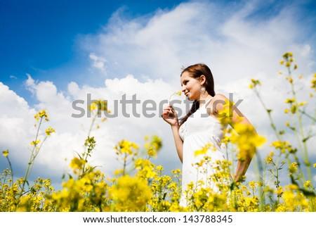 Beautiful Woman in white dress holding a rape flower. Rape Field. Yellow Field. rapeseed plantation. Canola Field. Girl In Field. Blue Sky. - stock photo