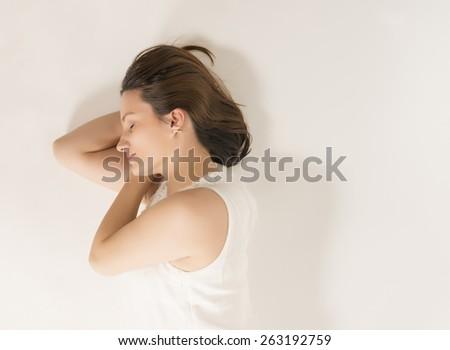 Beautiful woman in white dress sleeping, studio shot on white background - stock photo