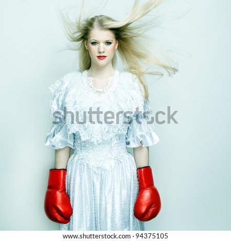 Beautiful woman in white dress with boxing gloves. Boxer bride - stock photo