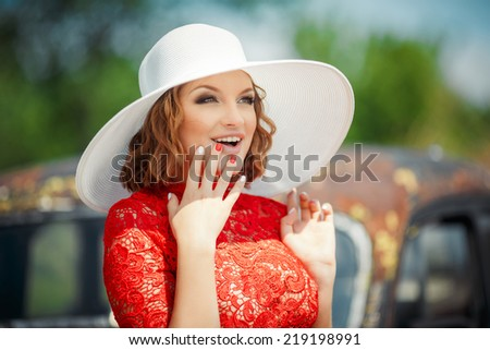 Beautiful woman in white hat expresses the joyful emotions. Female sexual appearance looks overlooking pine. Close up of a younger woman in a red dress and a white hat. - stock photo