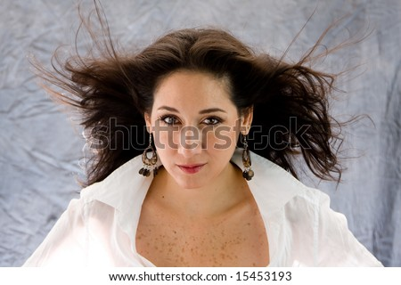 Beautiful woman in white with wind blowing through her long hair - stock photo