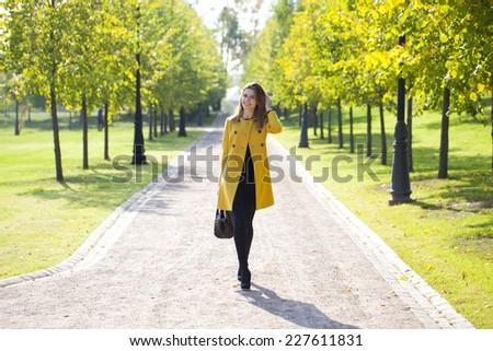 Beautiful woman in yellow coat walking autumn street - stock photo