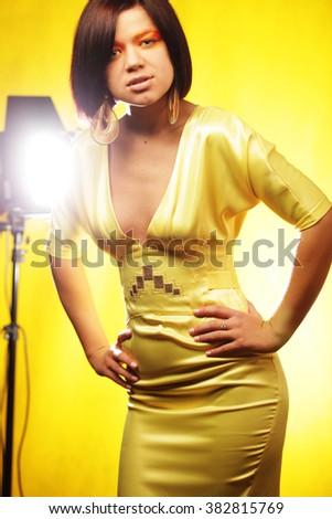 Beautiful woman  in yellow dress on yellow background - stock photo