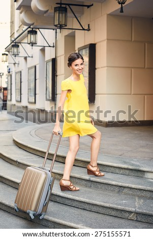 Beautiful woman in yellow dress with the suitcase at the entrance to the hotel
