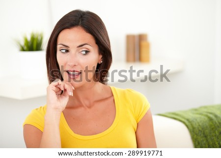 Beautiful woman in yellow shirt looking away from the camera with her mouth open - indoors - stock photo