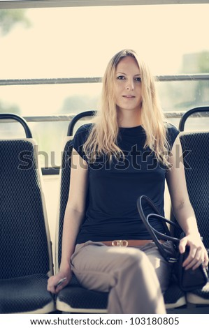 Beautiful woman inside a train or bus. Young passenger - stock photo