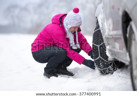 Beautiful woman  installing snow chain on her car - stock photo