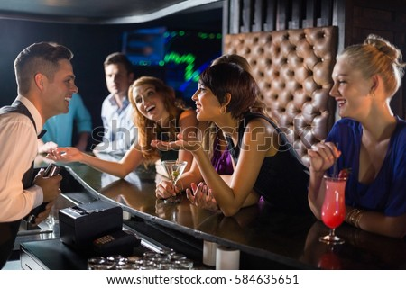 Beautiful woman interacting with waiter at bar counter in bar