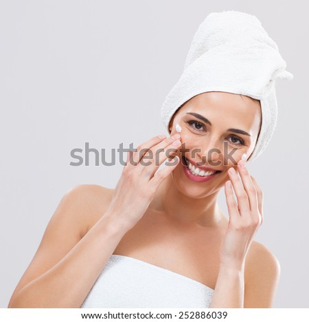 Beautiful woman is  applying lotion on her face.Skin care - stock photo
