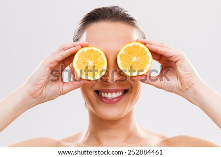 Beautiful woman is covering her eyes with slices of lemon.Lemon for your beauty and health!