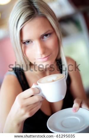 Beautiful woman is drinking coffee, looking into camera, very shallow depth of field