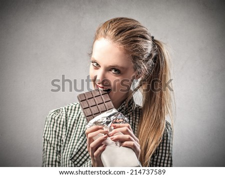 beautiful woman is eating a chocolate bar - stock photo