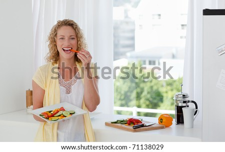 Beautiful woman is eating vegetables at home - stock photo