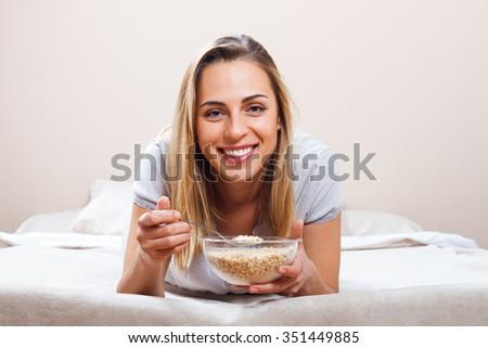 Beautiful woman is having breakfast in bed.Healthy breakfast  - stock photo