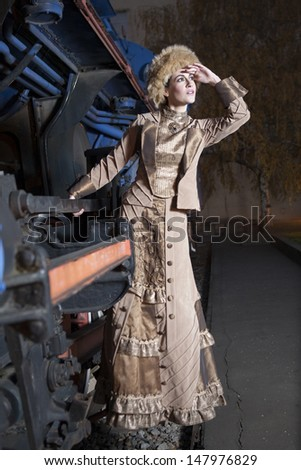 beautiful woman is holding a train and looking into the distance, 1910s - stock photo