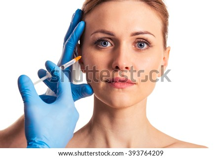 Beautiful woman is looking at camera, surgeon in blue medical gloves is making an injection in face, isolated on a white background - stock photo