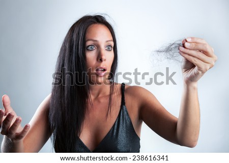 Beautiful woman is looking shocked on her lost hair - stock photo
