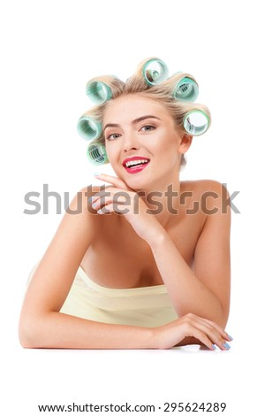 Beautiful woman is lying and smiling. She is making hairstyle with rollers. The lady is touching her face with her hand gently. Isolated on background - stock photo
