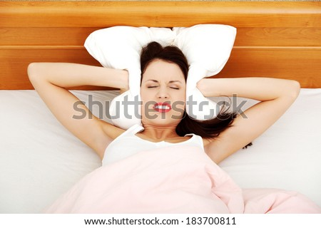 Beautiful woman is lying in bed and covering her ears with pillow. Noise or insomnia concept. - stock photo