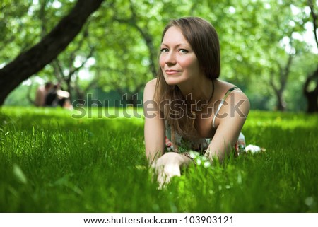 Beautiful woman is lying on the grass
