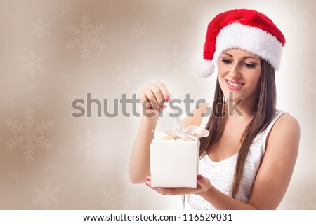 beautiful woman is opening a christmas gift - stock photo