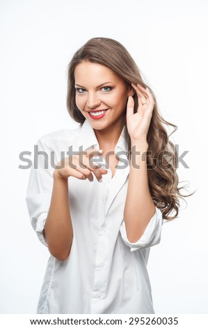 Beautiful woman is pointing her finger forward. She is raising hand to her ear wily. The lady is laughing. Isolated on background