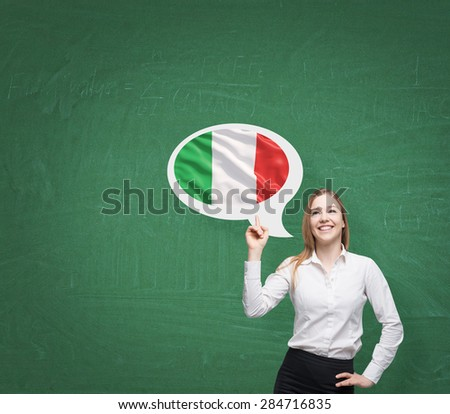 Beautiful woman is pointing out the thought bubble with Italian flag. Green background. - stock photo
