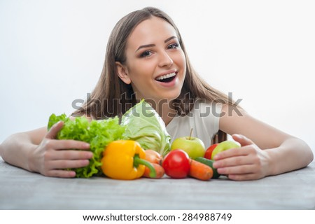 Beautiful woman is raking vegetables and fruits gradually. She is smiling and looking at the camera. Isolated on a white background