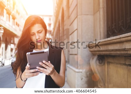 Beautiful woman is reading text message on touch pad while is standing on the street in spring day, stylish hipster girl tourist is using tablet computer for navigation during walk in the city abroad - stock photo
