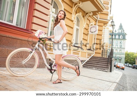 Beautiful woman is riding the bicycle and posing. She is looking aside mysteriously. The lady is flirting with someone. Copy space in right side - stock photo