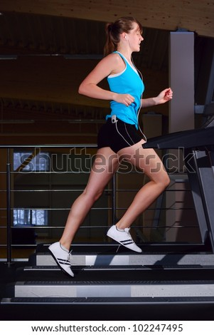 beautiful woman is running on the treadmill - stock photo