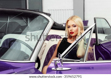 Beautiful woman is sitting in the car and touching her blond hair - stock photo