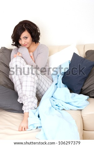 beautiful woman is sitting on the sofa an reading a book