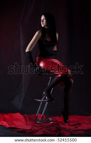 Beautiful woman is sitting on the stool in the dark room.