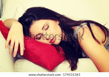 Beautiful woman is sleeping on red pillow. Pretty girl on the couch.  - stock photo