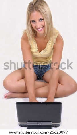 beautiful woman is smiling in front of the laptop computer - stock photo