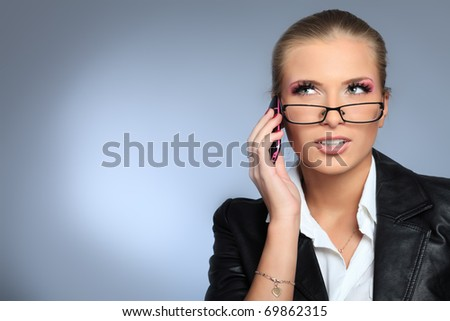 Beautiful woman is talking on the phone. Studio shot over grey background.