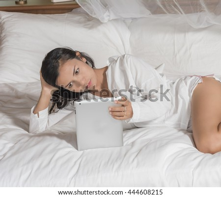 Beautiful  woman is using tablet in bedroom