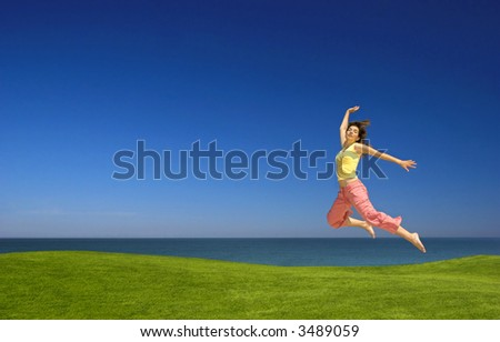 Beautiful woman jumping on a green field