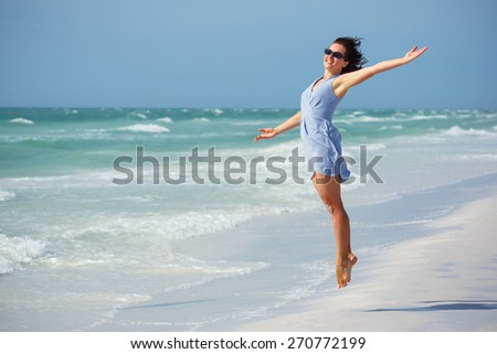 Beautiful woman jumping on Florida Beach. Vacation Concept - stock photo