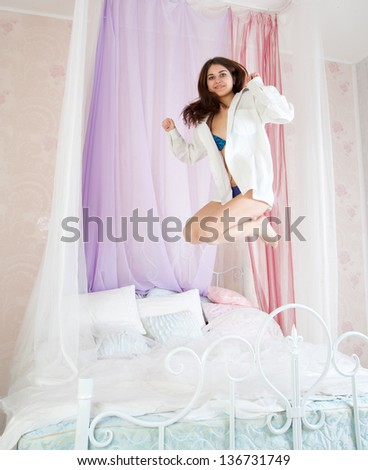 Beautiful woman jumping on the bed - stock photo