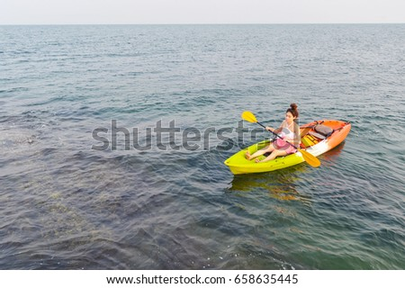 Beautiful woman kayaking in the sea.