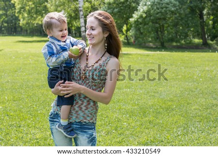 Beautiful woman keeps on hand her two years old child against green trees and grass. They look at each other and smile - stock photo