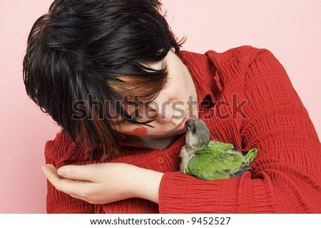 beautiful woman kissing baby parrot - stock photo
