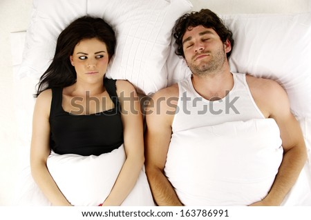 Beautiful woman laid in a white bed awake next to her sleeping snoring boyfriend isolated on a white background - stock photo