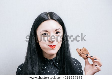Beautiful woman laughing and eating cookies. On a gray background. - stock photo