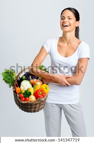 Beautiful woman laughing and holding a basket full of fresh organic vegetables - stock photo