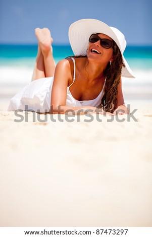 Beautiful woman laying at the beach and smiling - stock photo