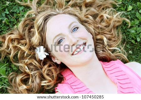 Beautiful woman laying in grass with flower in her hair. - stock photo